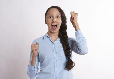 kobieta w koszuli wyrażająca szczęści - wielki uśmiech na twarzy