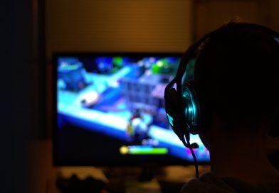 mężczyzna grający na komputerze, na ekranie jakaś gra, mężczyzna ma słuchawki, jest ciemno w pomieszczeniu, ekran rozświetla pomieszczenie