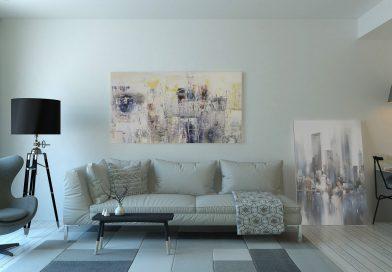 mieszkanie - biała ściana, jasny obraz, jasna sofa, biały dywan, czarna lampa, światło bije od lewej strony