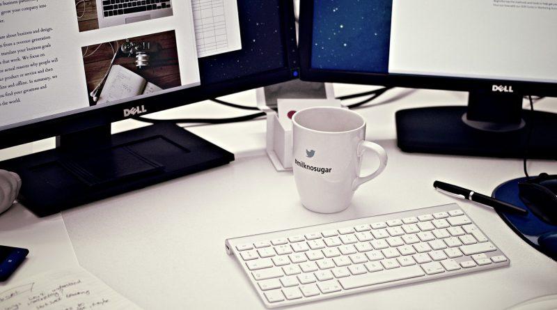 komputer z wynajmu komputerów; dwa monitory, kubek i klawiatura stoją na biurku